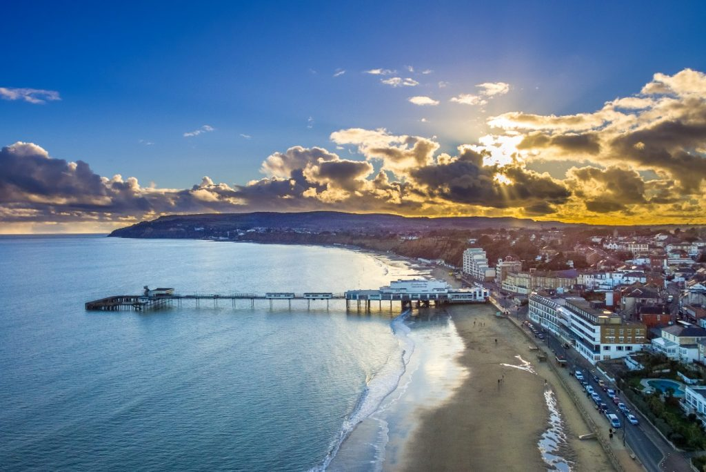 An aerial shot of Sandown Bay pier, beach and waterfront buildings while the sun is shining through some clouds